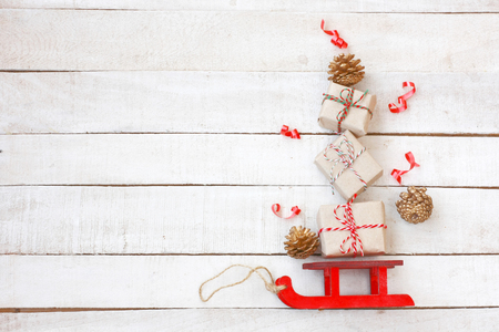 Christmas red sleigh driven by gift box, golden cones, streamers on white wooden table, vintage style, view from above, New Year composition