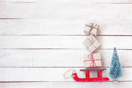 Christmas red sled carried gift box, spruce on white wooden table, vintage style, top view, new year composition, Banco de Imagens
