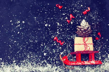 red Christmas sleigh carrying gift box, pine cone, streamer on black surface, vintage style new year night composition