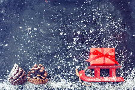 red Christmas sleigh carrying gift box, pine cones on black surface, snow, vintage style new year night composition Stock Photo