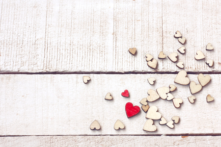 Valentine's day congratulation card,  bunch of different plywood hearts on white wooden table, top view Stock Photo