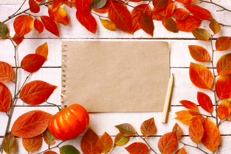 autumn background with branches and colorful autumnal leaves, notebook paper sheet and pencil on white wooden table, top view