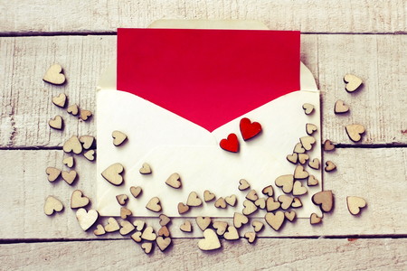 Valentine's day congratulation card, different plywood hearts, envelope with blank red paper on white wooden table Stock Photo