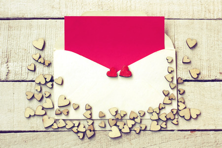 Valentine's day congratulation card, bunch of different plywood hearts, envelope with blank red paper on  white wooden table Stock Photo