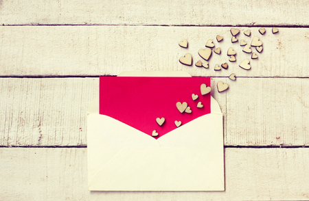 Valentine's day congratulation card,  bunch of different plywood hearts on  white wooden table, envelope with empty red texture paper