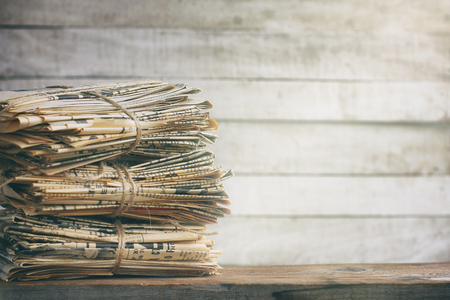 Waste paper in vintage style. Old newspaper abstract background. Paper trash on wooden table