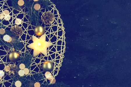 Christmas card with candle, fir tree branches, gold balls, on dark background, blurred light