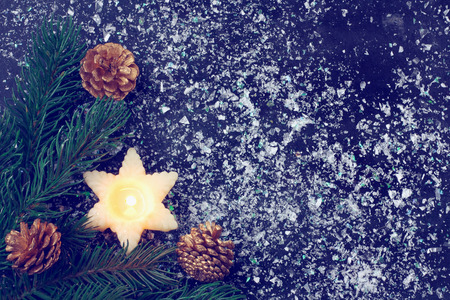 Vintage Christmas card with candle, fir tree branches, golden cones on dark background Stock Photo