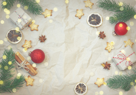 Christmas vintage background, fir tree branches, gift box, red balls, cinnamon, anise, dry orange, star shape cookie on crumpled paper, top view Stock Photo