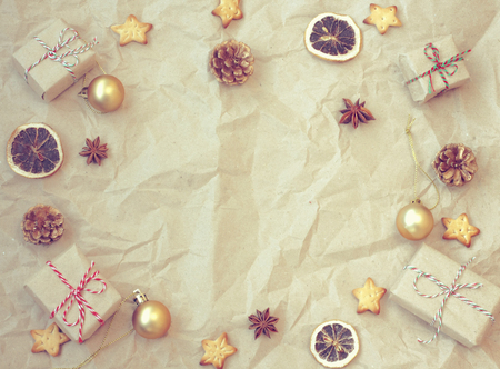 Christmas vintage background, gift box, golden balls, anise, dried orange, cookie star shape, cones  on crumpled kraft paper Stock Photo