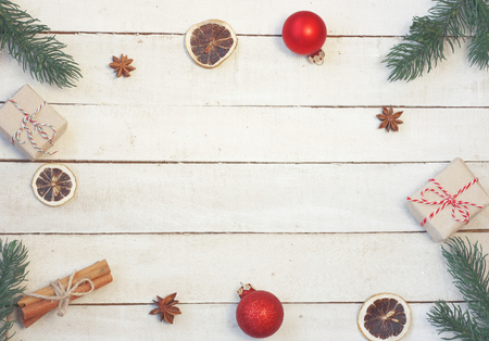 Christmas vintage background, fir tree branches, gift box, red balls, cinnamon, anise, dry orange, on white wooden table, top view