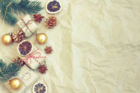 Christmas vintage border, Christmas tree branches, gift box, golden balls, anise, dry orange, cones on crumpled craft paper