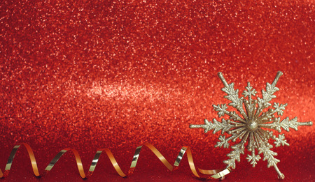 Christmas red background. New year decoration. Vintage golden snowflake and ribbon. Bokeh defocused light effect
