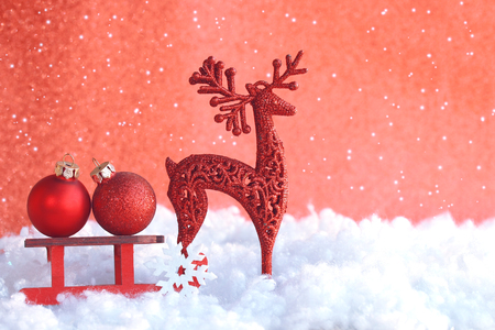 Christmas red greeting card, toy wooden sled, two ball, deer, in snow, vintage retro style Stock Photo