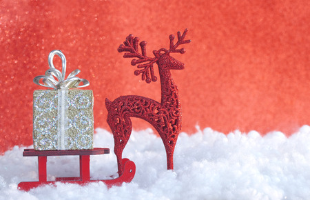 Christmas greeting card, red toy wooden sled, gift box, deer, in snow, vintage New year Stock Photo