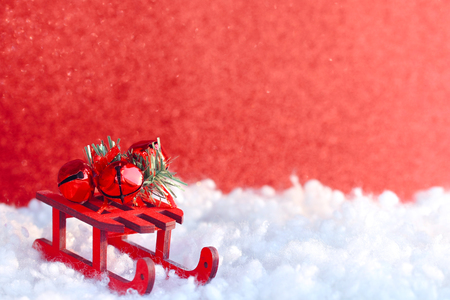 Christmas red greeting card, toy wooden sleigh, decorative bells, in snow, retro style Stock Photo