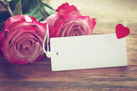 Valentine's day background, two pink roses, white empty label on wooden table, vintage toned