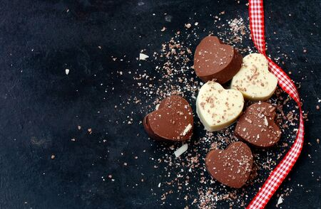 Valentines day background, home made chocolate dark and white hearts and ribbon, on black shabby surfase Stock Photo
