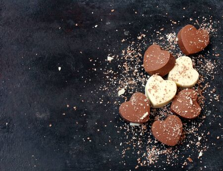 Valentines day background, home made chocolate dark and white hearts on black shabby surfase, top view