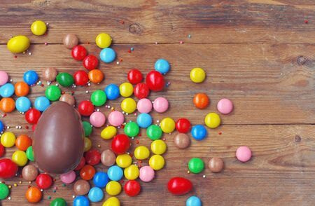 Easter chocolate egg, colorful candy on wooden table. Delicious dessert holiday food, top view