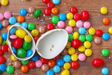 Easter chocolate egg, colorful candy on wooden table. Delicious dessert holiday food Stock Photo