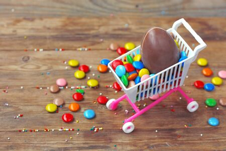 Easter chocolate egg, colorful candy on wooden table. Easter sale concept. Delicious dessert holiday food