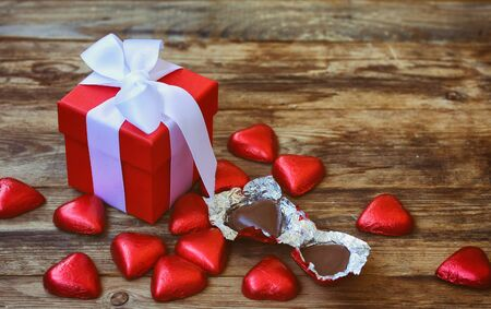 Valentine's day greeting card, red gift box and chocolate heart on wooden table, selective focus