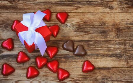 Valentine's day greeting card, red gift box and chocolate heart on wooden table, top view