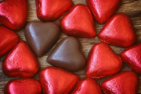 Valentine's day background, chocolate red heart on wooden table, close up, top view Stock Photo