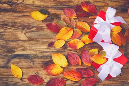 Colorful autumn leaves and two red gifts boxes in retro style on wooden background. Autumn composition.Top view.