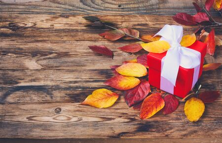 Colorful autumn leaves and red gift box in retro style on wooden background. Autumn composition.Top view.
