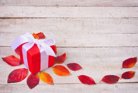 Colorful autumn gift box in retro style. Autumn composition. White wooden table background. Top view. Stock Photo