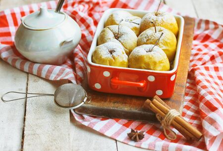 Baked apples on white rustic wooden table. Delicious fruit cake. Delicious snack. Christmas dessert. Sweet food.