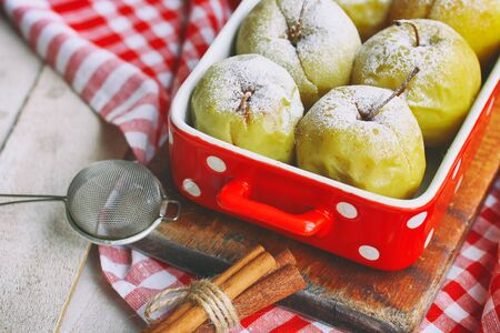 Baked apples on white wooden table top view. Delicious fruit cake. Delicious snack. Christmas dessert. Sweet food. Rustic wooden table background