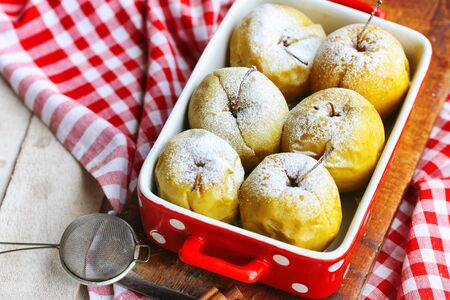 Baked apples on white rustic wooden table. Delicious snack. Christmas dessert. Sweet food. Top view.