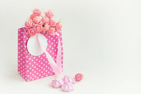 pink paper bag with bouquet of roses, holiday gift card, marshmallows, white background