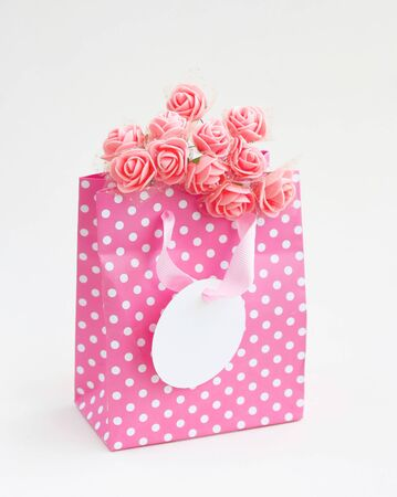 pink paper bag with bouquet of roses, holiday gift, white background