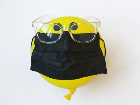 protection against coronavirus, balloon with glasses and medical mask on a white background