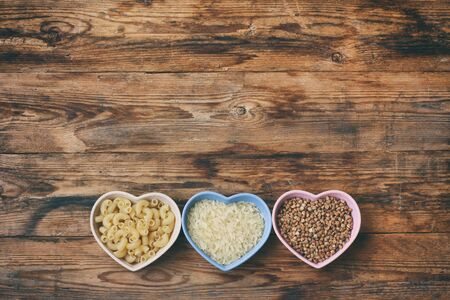 rice, pasta, buckwheat, in bowl  heart shape, grocery products on wooden table, top view, space for text Stock Photo