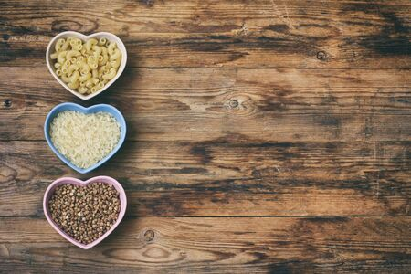 rice, pasta, buckwheat, in bowl heart shape, grocery products on wooden table, top view, space for text