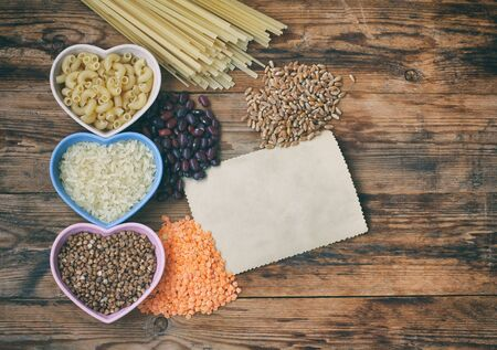 rice, pasta, buckwheat, beans and wheat, grocery products on  wooden table, top view, space for text Stockfoto