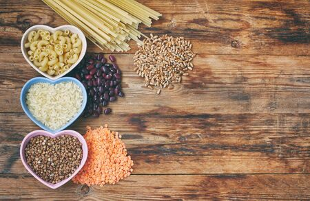 rice, pasta, buckwheat, beans, wheat, grocery products on wooden table, top view, space for text
