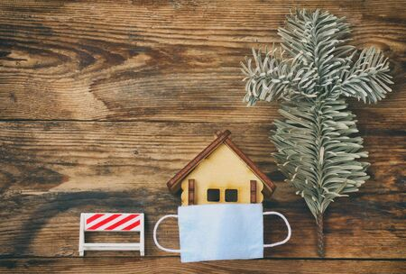 small toy house in medical mask, wood background, stay home concept