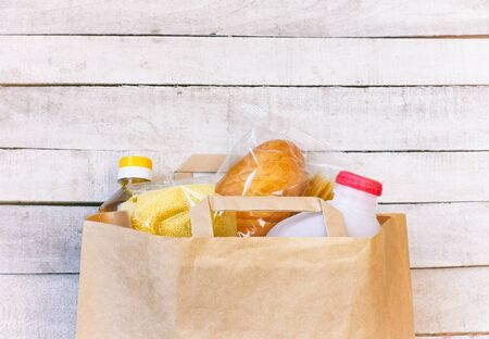paper bag with a set of products, sunflower oil, milk, bread, cereals and pasta, donation and delivery, on a white wooden table