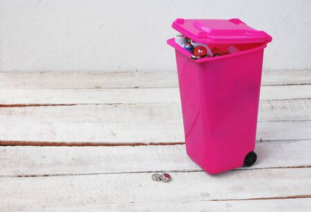 batteries in a trash can, recycling concept, white wooden table Stock Photo