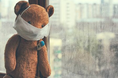 toy old bear in medical mask with thermometer sitting on window, coronavirus isolation concept