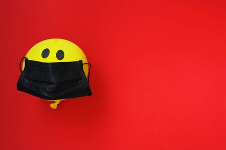 antivirus protection concept, yellow balloon in black medical mask, on red background Stock Photo