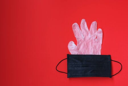 antivirus protection concept, black medical mask, rubber protective disposable gloves on red background