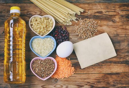 rice, pasta, buckwheat, beans, wheat, egg, sunflower oil, grocery products on wooden table, top view, space for text Stockfoto