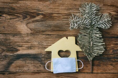 small toy house in medical mask, wood background, stay home, quarantine concept Stock Photo